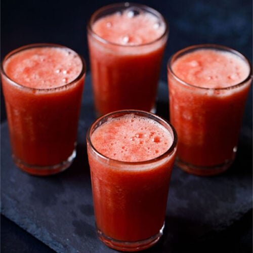 watermelon juice in four glasses or a dark blue table
