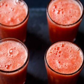 four tall clear glasses filled with watermelon juice on a black background