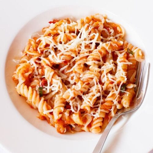 arrabiata pasta in a deep dish serving plate wit a silver fork by the side