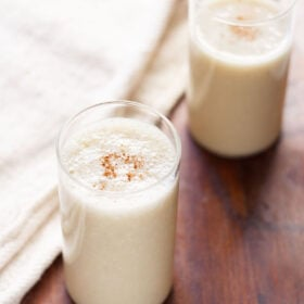 banana milkshake in two glasses with a light sprinkle of ground cinnamon on a dark brown table with a cream jute napkin by side