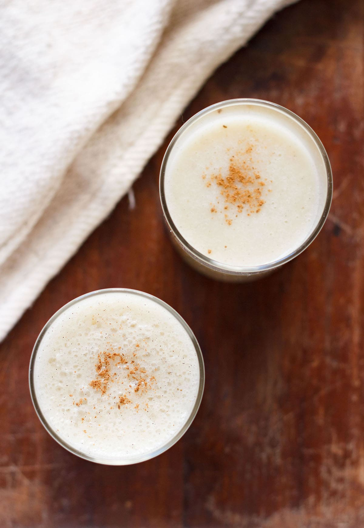 overhead shot of banana milkshake in two glasses with a light sprinkle of ground cinnamon on a dark brown table