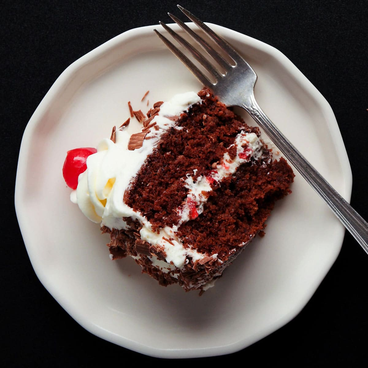 overhead shot of a slice of black forest cake on its side on a white dessert plate with a silver fork