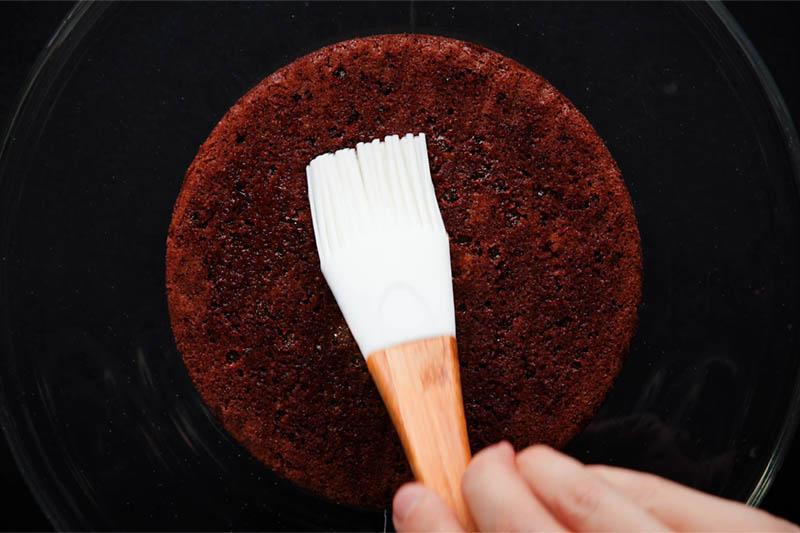 brushing bottom layer of chocolate sponge with sugar syrup