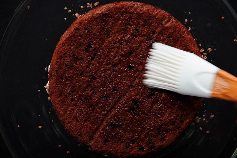 second layer of chocolate sponge being brushed with sugar syrup