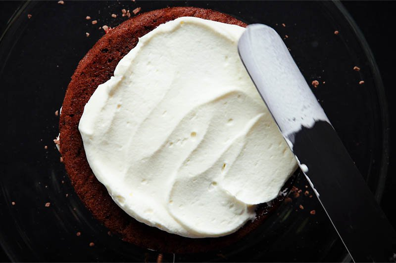 more whipped cream being added to the top layer with an offset spatula