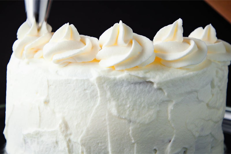 piping rosettes of whipped cream around the top of the frosted eggless black forest cake