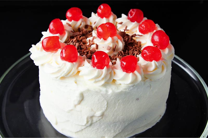 whole cherries and chocolate shavings added to the top of the black forest cake