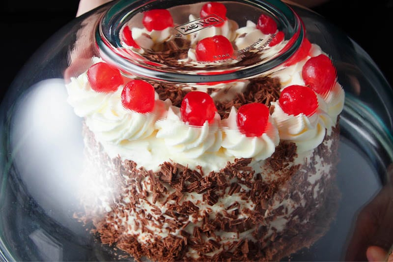 glass bowl placed over the decorated black forest cake to protect it during refrigeration