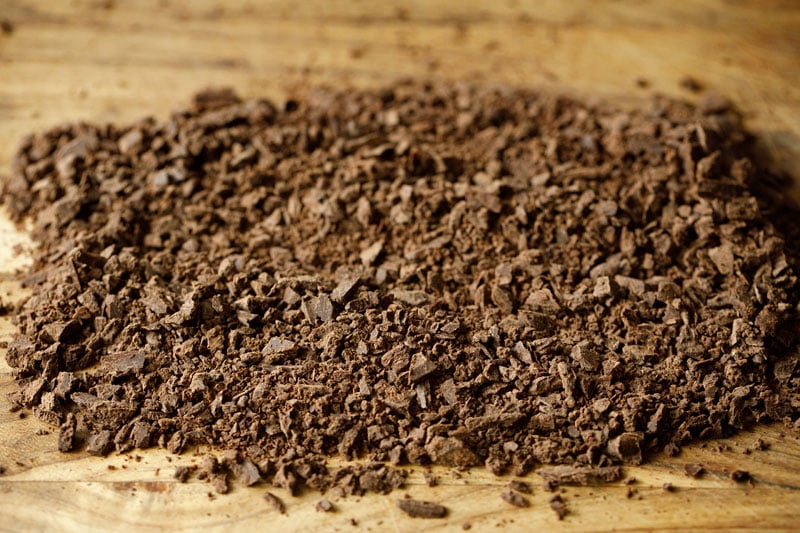 finely chopped dark chocolate on wooden tray