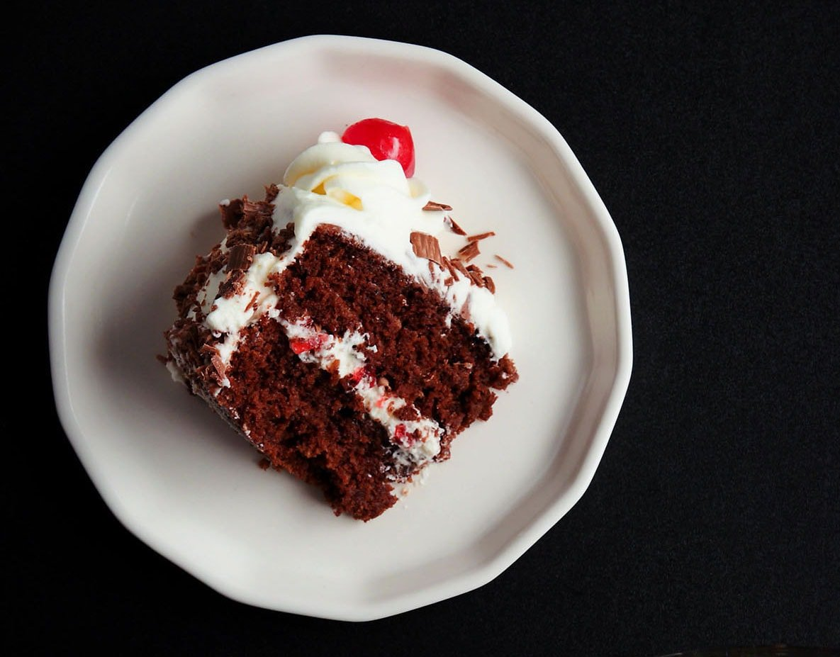 overhead shot of one slice of black forest cake on its side on a white plate