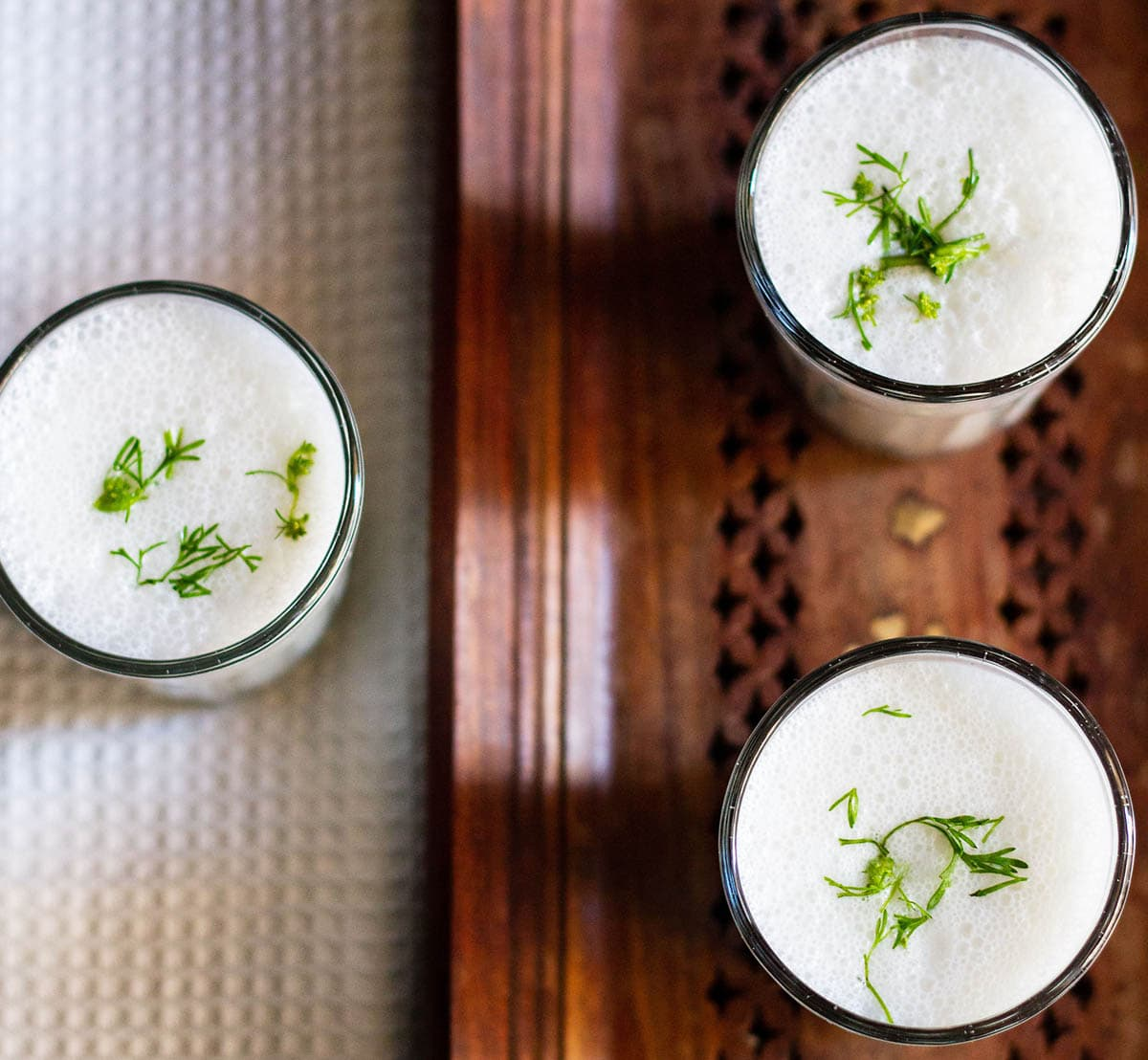 overheat shot of small three glasses filled with masala chaas placed on a wooden tray next to a white linen