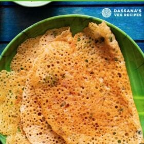 overhead shot of lacy crispy stacks of folded oats dosa on a green plate on a dark blue tray