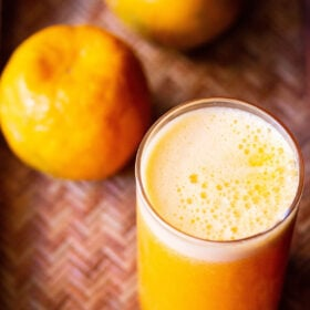 orange juice in a glass with two oranges on top on a cane tray