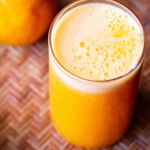orange juice in a glass with orange on top on a cane tray