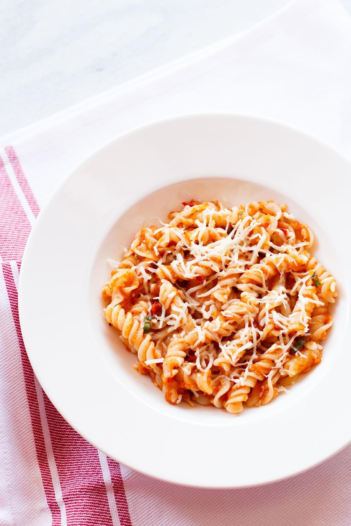 pasta arrabiata in a deep dish on a red bordered white napkin