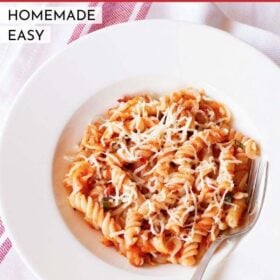 pasta arrabiata in a deep dish serving plate wit a silver fork by the side