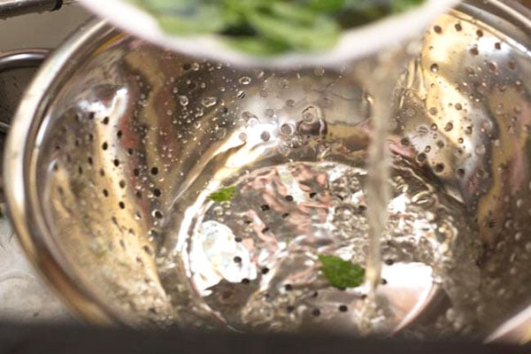 water from the methi leaves being poured in a steel colander