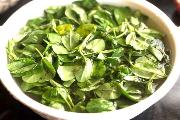 methi leaves soaking in water in a white bowl