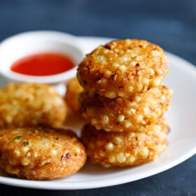 closeup shot of a stack of sabudana vada on top of each other in a white plate with red chilli sauce in a white bowl