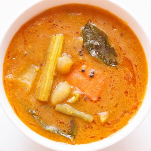 overshot shot of sambar filled in a white bowl placed on white plate