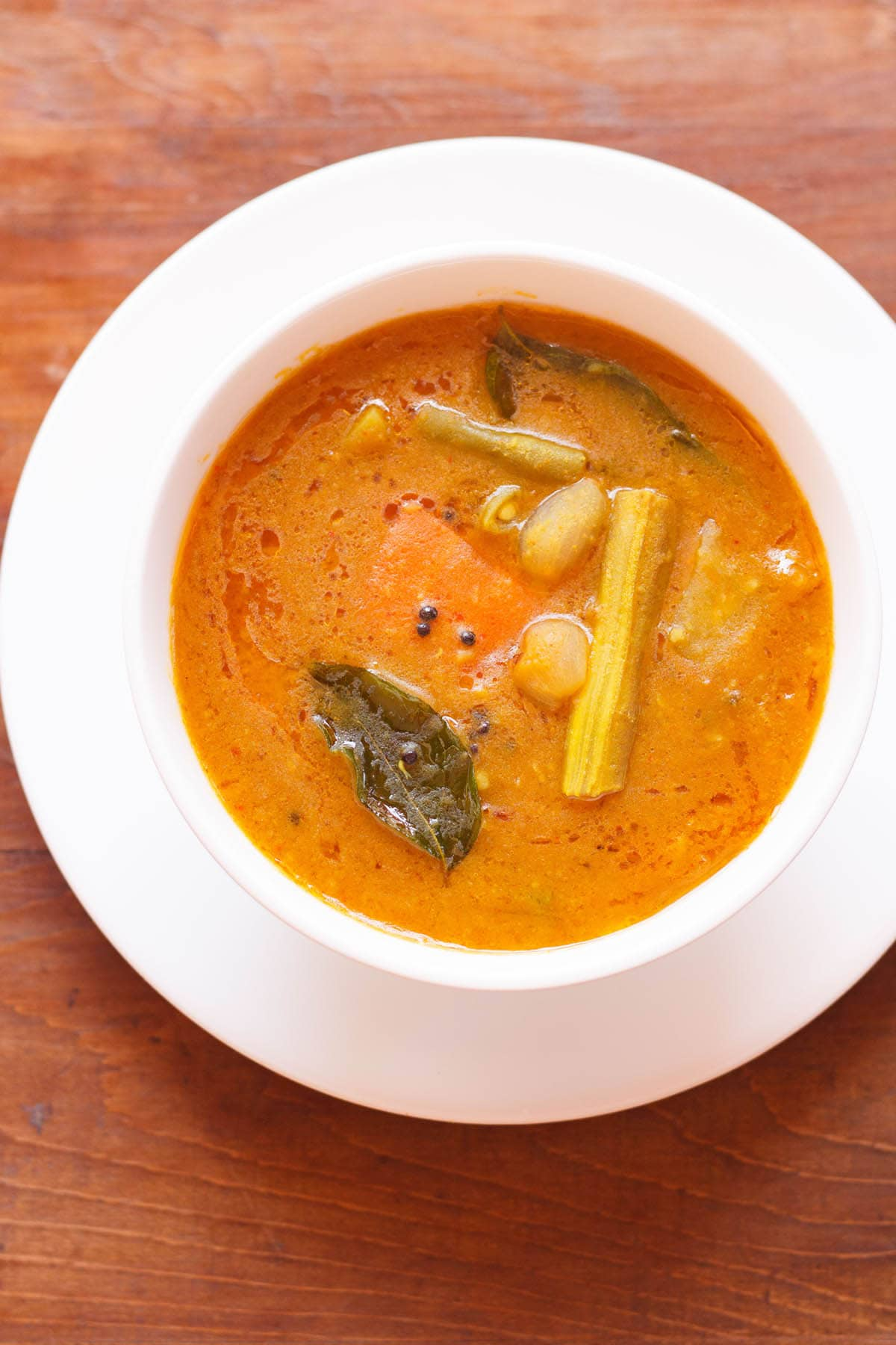 overhead shot of sambar filled in a white bowl placed on white plate on a brown wooden board