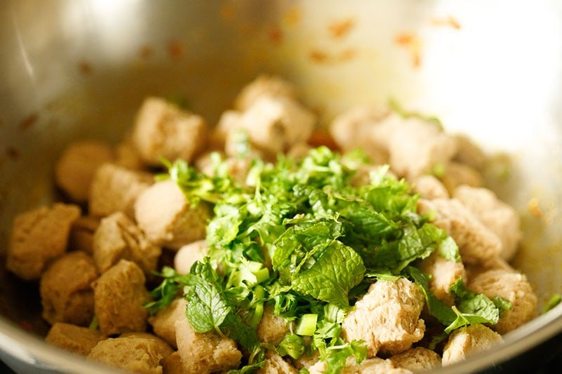 fresh herbs and soy chunks added to pot for meal maker curry
