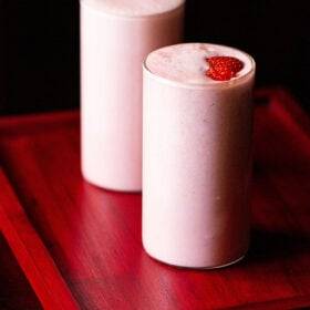 strawberry milkshake topped with strawberry slices in two glasses on a reddish pink tray