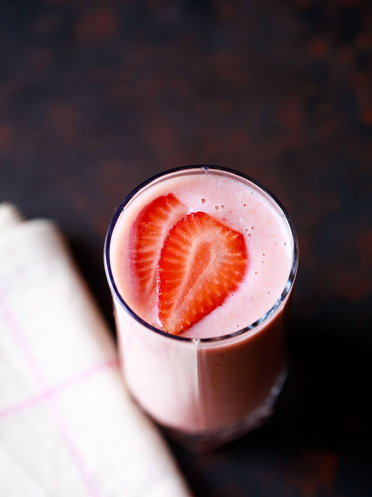 strawberry smoothie in a glass topped with strawberry slices with a cream napkin on a dark black-brown board