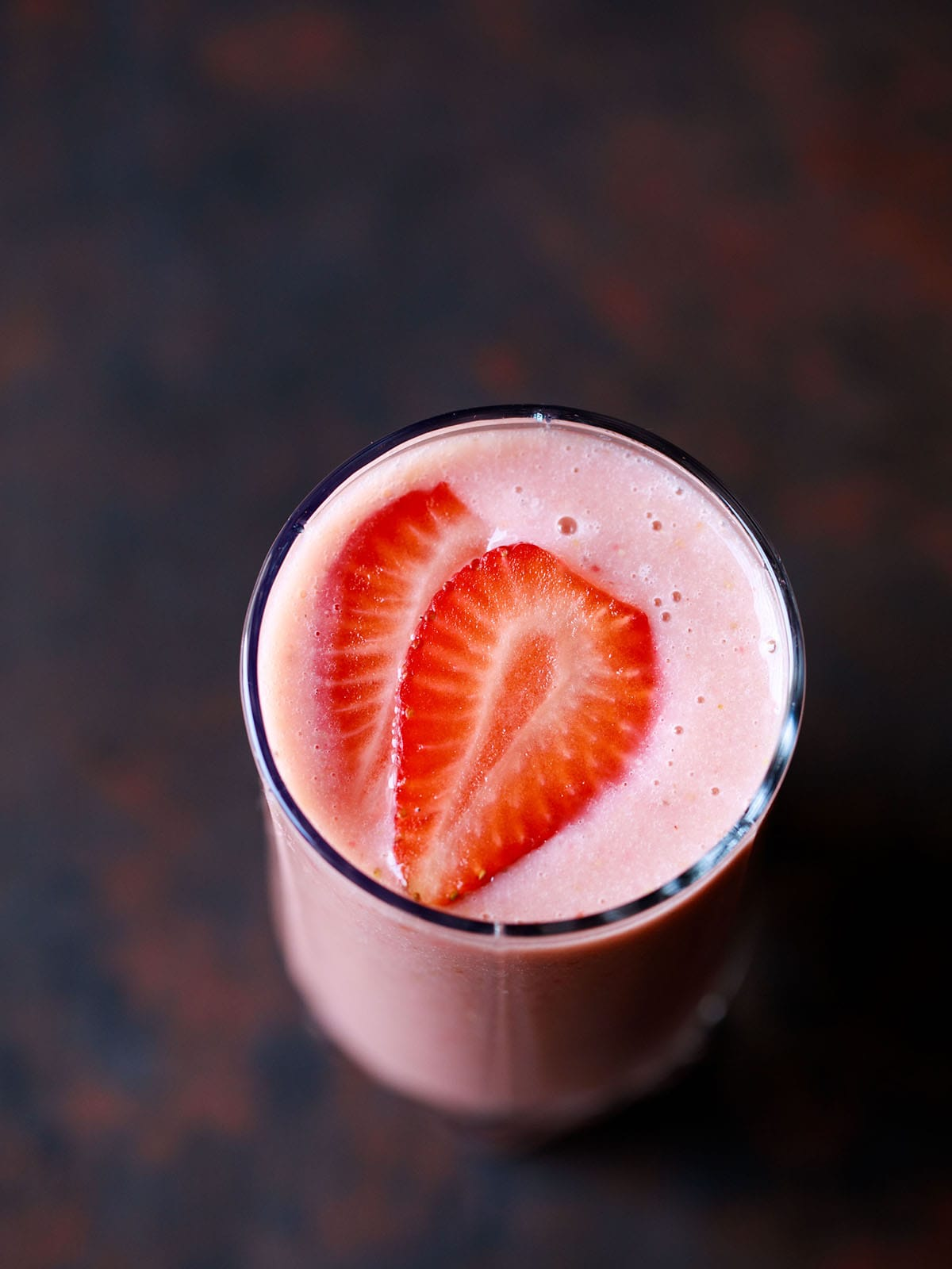 strawberry banana smoothie in a glass topped with strawberry slices on a dark black-brown board
