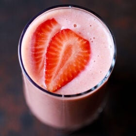 closeup overhead shot of strawberry smoothie in a glass topped with strawberry slices on a dark black-brown board