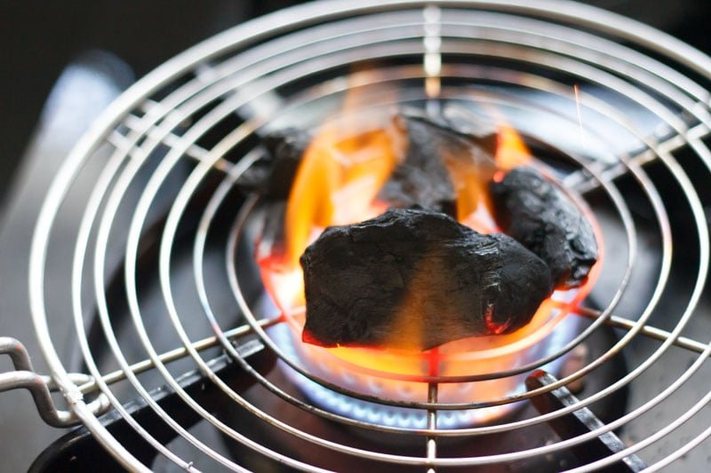coal pieces on a round wired tray on stove-top burner