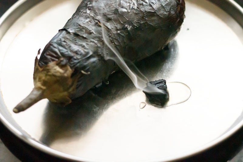 smoked charcoal with oil dripping on it and sides placed close to the roasted eggplant in a steel plate