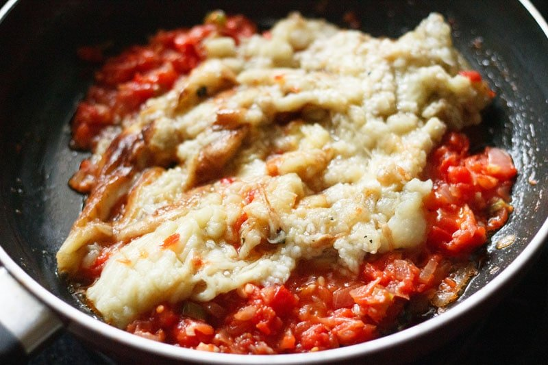 chopped cooked eggplant on the tomatoes in the pan
