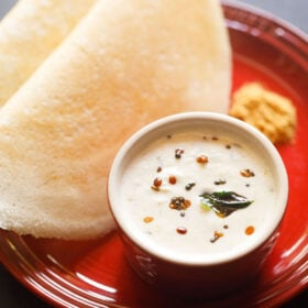 a small white bowl of coconut chutney on a red plate with two dosa