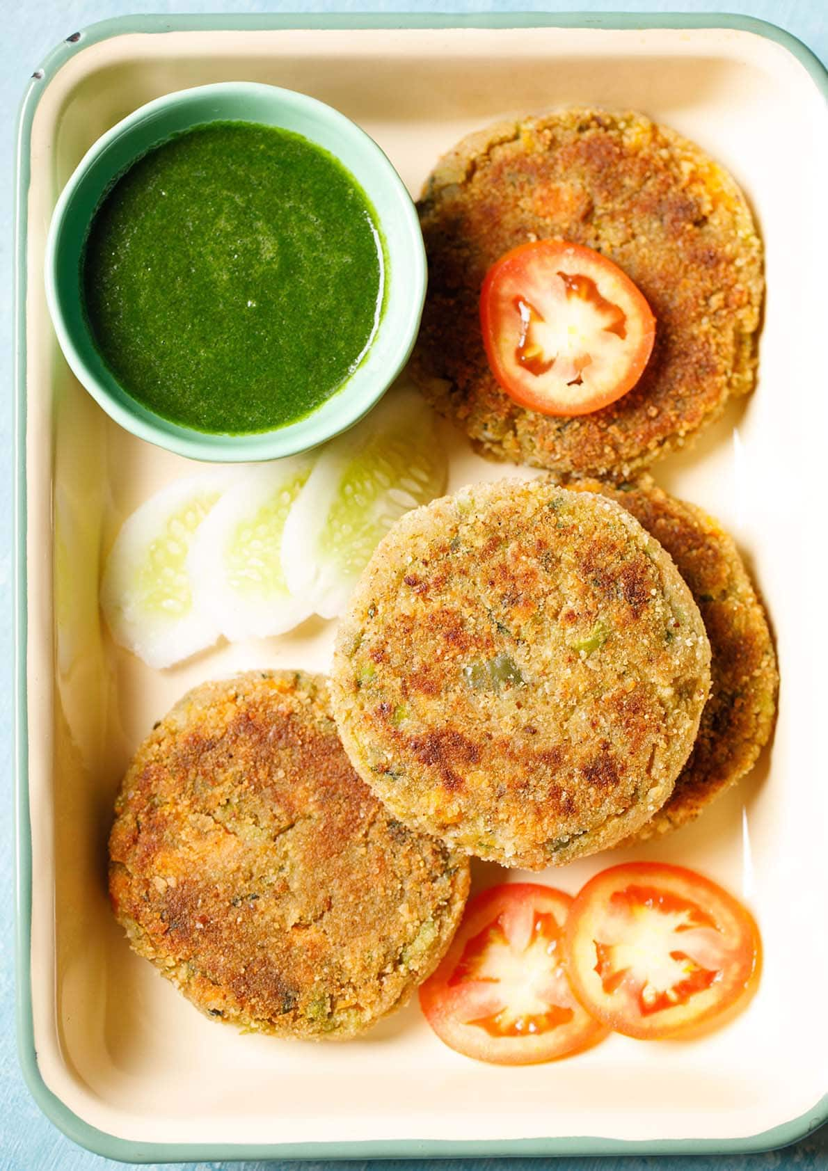 veg cutlet placed on a tray with a few slices of tomatoes, cucumber and a light green bowl filled with green chutney