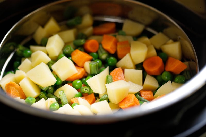 steamer pan with veggies placed on trivet in the instant pot