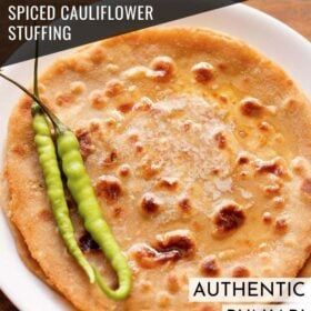 overhead shot of gobi paratha in a white plate topped with two green chillies at the side with text layovers