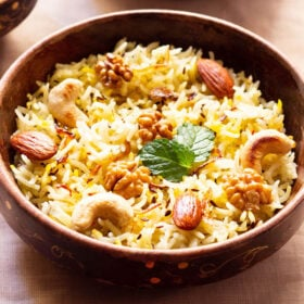 Kashmiri pulao in a brown bowl garnished with fried nuts and onions and a few fresh mint leaves next to a bowl of tomato raita on a beige table cloth