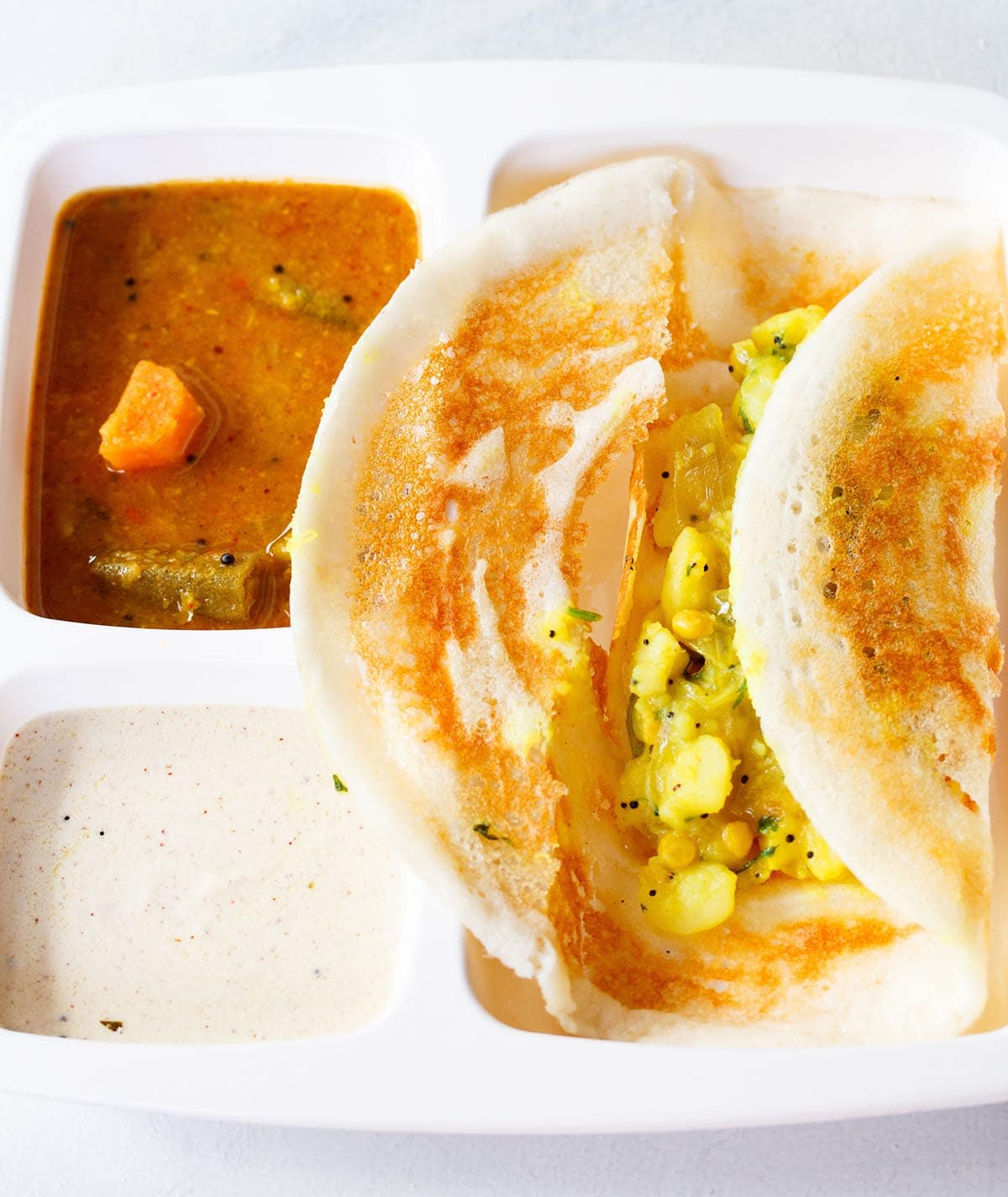 masala dosa opened showing the potato stuffing in a white partitioned tray with sambar and coconut chutney