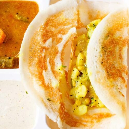 masala dosa opened showing the potato masala stuffing in a white partitioned tray with sambar and coconut chutney