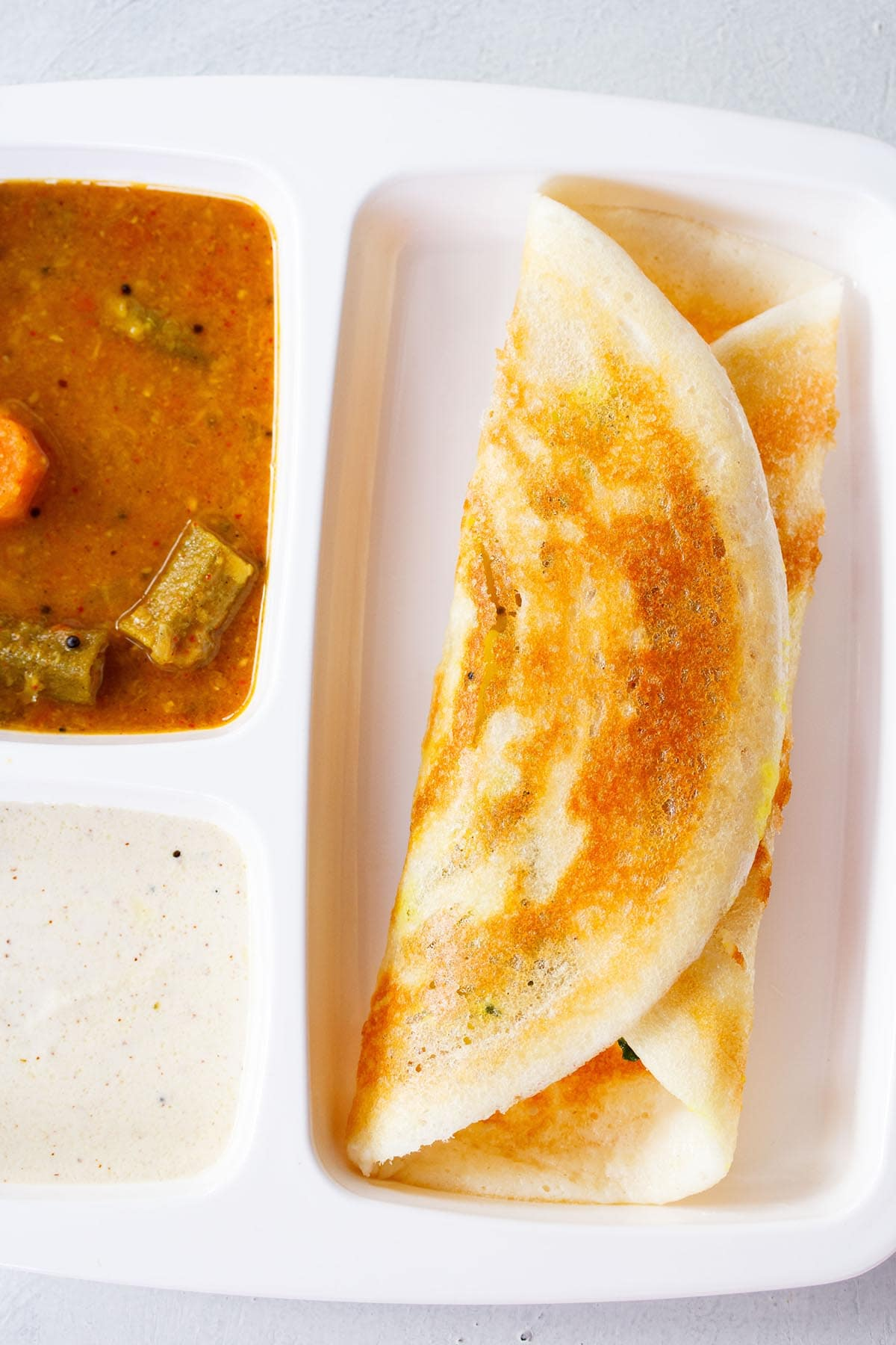 folded masala dosa in a white partitioned tray with sambar and coconut chutney