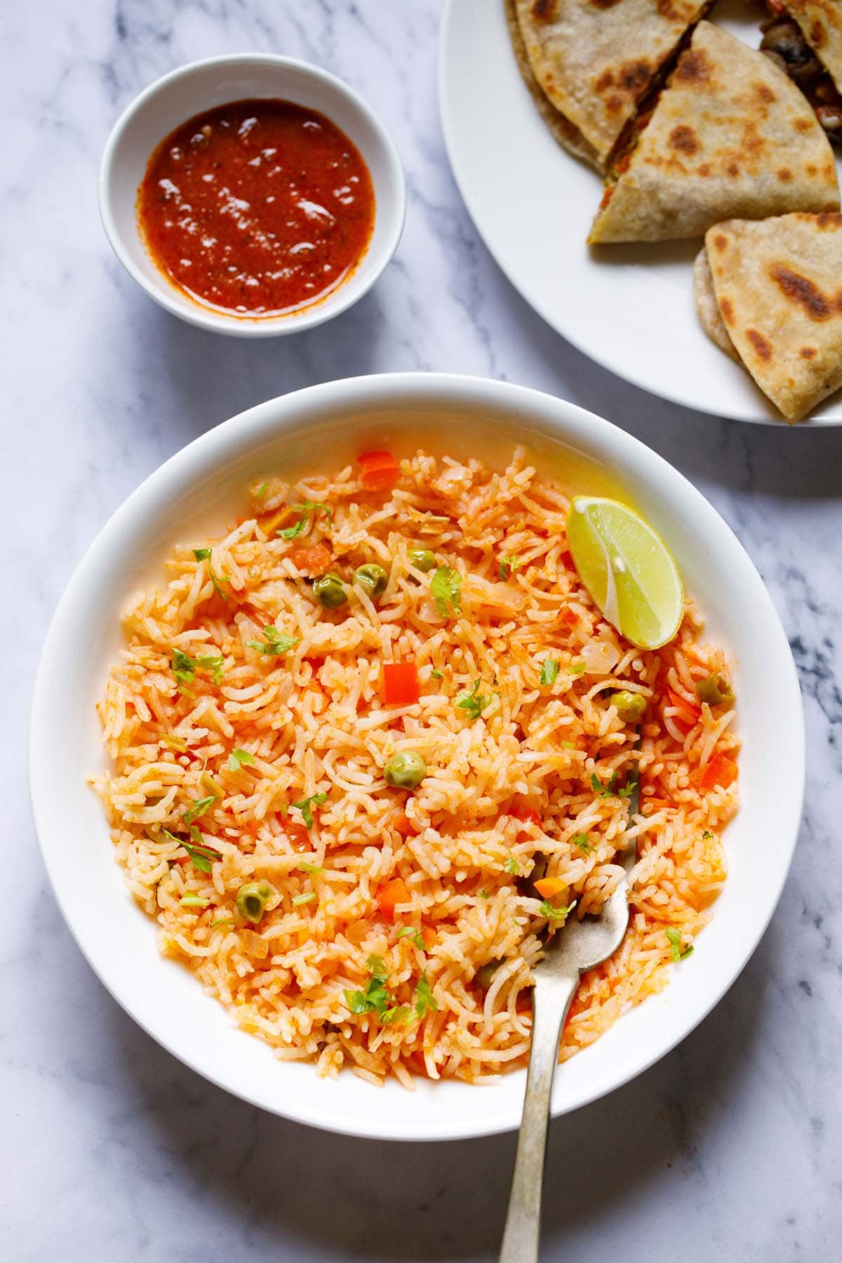 overhead shot of mexican rice with a lemon wedge and a brass fork in the rice in a large white bowl with enchilada sauce and quesadilla on top