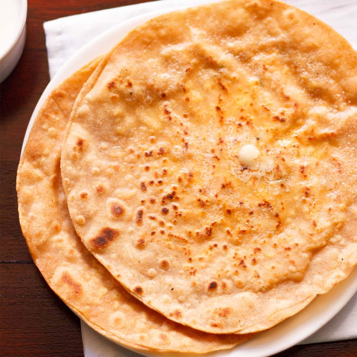 two paneer paratha with butter melting on top on white plate placed on white napkin