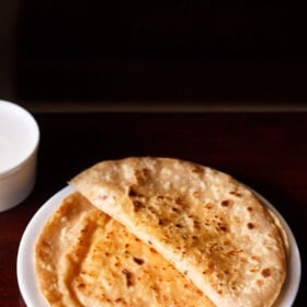 folded paneer paratha on top of a paneer paratha on a white plate on a dark brown table