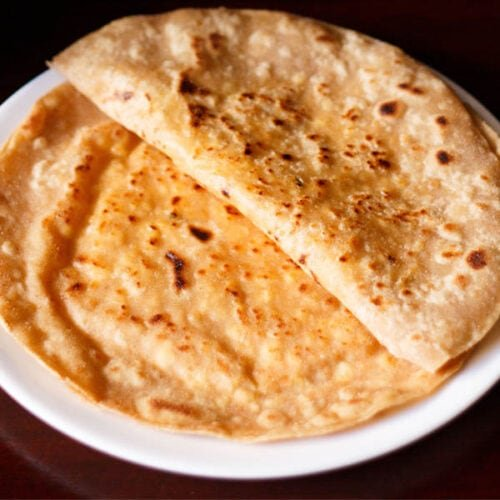 folded paneer paratha on top of a paneer paratha on a white plate