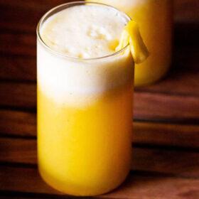 fresh pineapple juice served in two glasses and garnished with fresh pineapple pieces