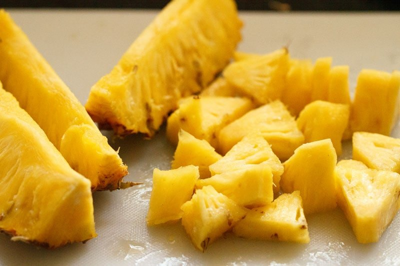 chopped pineapple pieces on a board