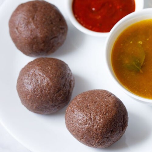 three ragi mudde balls on a white plate with two small bowls of saaru and chilli chutney