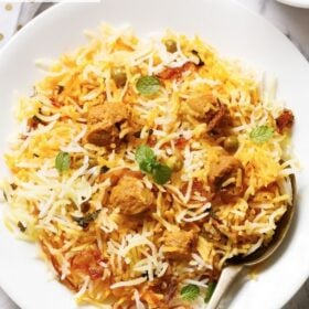 soya biryani in a white plate with a brass spoon on the plate with text layovers