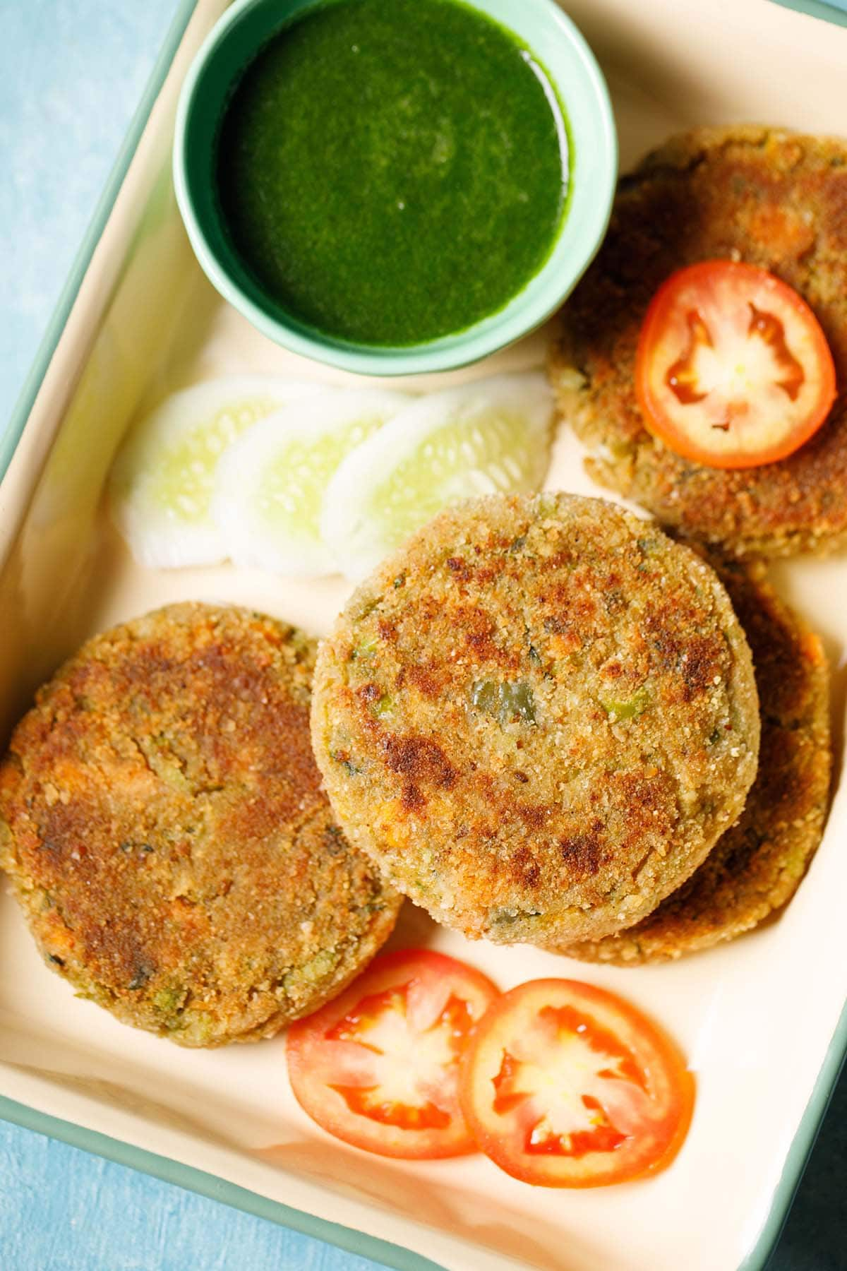 closeup shot of veg cutlet cutlet placed on a tray with a few slices of tomatoes, cucumber and a light green bowl filled with green chutney